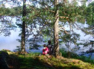 Två personers sitter vid tallar och ser ut över vatten. De har ryggen mot kameran.