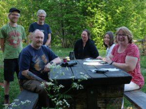 Styrelsens medlemmar sitter vid ett bord ute i naturen