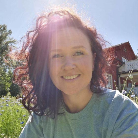 Elin Iderström med mörkt hår och gråblå tröja i solen framför ett rött hus.